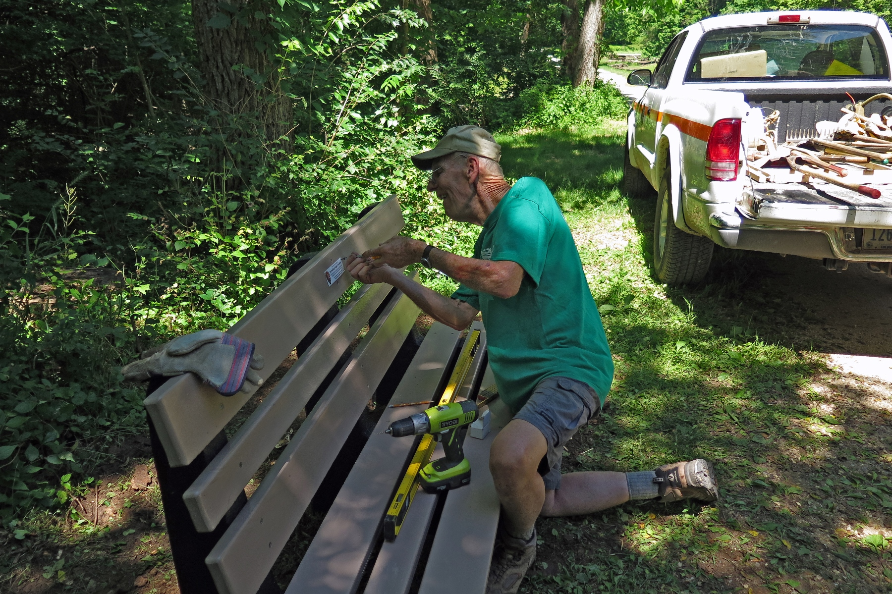Volunteer attaches plaque to bench